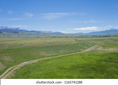 Broad green farming fields in western Wyoming with Rocky Mountains in the distance.