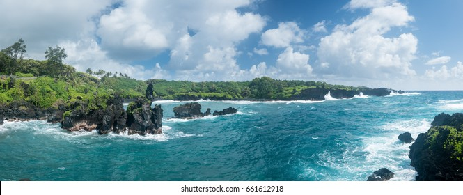 Broad panorama of vegetation covered rocks tower above the ocean at Waianapanapa State Park on the road to Hana in Maui, Hawaii