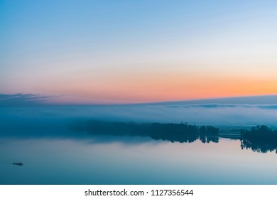 Broad river flows along diagonal shore with silhouette of forest and thick fog. Tree drifts with flow. Orange and pink glow in predawn vanila sky. Morning atmospheric landscape of majestic nature.