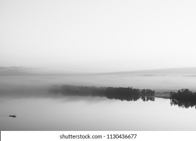 Broad river flows along diagonal shore with silhouette of forest and thick fog in grayscale. Tree drifts with flow. Minimalistic monochrome landscape of majestic nature. Morning milky atmosphere.