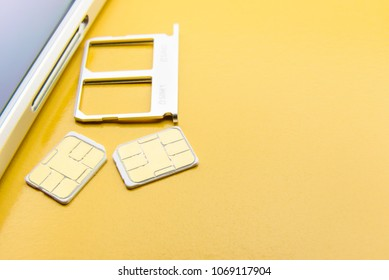 Broadband 5G mobile communication technology concept : SIM card tray / dual SIM card slot with two nano SIM cards on yellow background. SIM stores international mobile subscriber identity IMSI number.