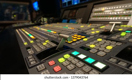 Broadcast television switcher in news studio with blur background.