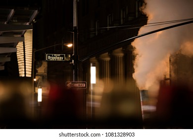 Broadway sign illuminated at night in Manhattan, New York. Steam coming out of the manhole on the right side.