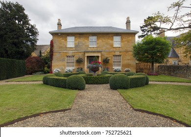 Broadway, UK: October 14, 2017: Front view of the exterior and garden of a detached house in the English Georgian architectural style  built with Cotswolds stone