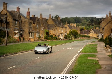 BROADWAY,WORCESTERSHIRE/ENGLAND-AUGUST 27 2018: An old vintage car drives through the village of Broadway in the Cotswolds England.