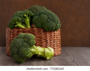 Broccoli cabbage in a wicker basket. A lot of broccoli in a wicker box on a brown background. Vintage broccoli for diet and healthy eating. Fresh raw broccoli.