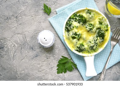 Broccoli cauliflower gratin in a white baking dish on a grey concrete,stone or slate background .Top view with copy space.