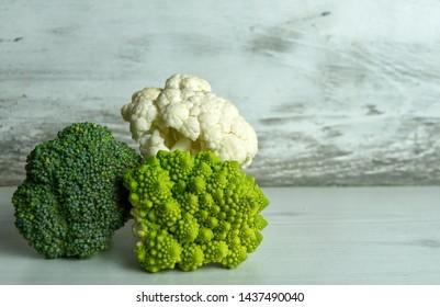 broccoli, cauliflower and romanesco cole lying on white kitchen worktop