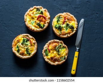 Broccoli cheddar mini savory pies on dark background, top view. Delicious appetizers, snack, tapas. Copy space