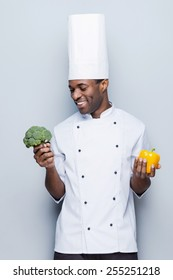 Broccoli or pepper? Cheerful young African chef in white uniform holding pepper in one hand and broccoli in another while standing against grey background