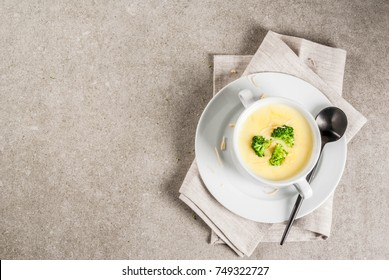 Broccoli, cheese and chicken soup, on gray stone table, copy space top view
