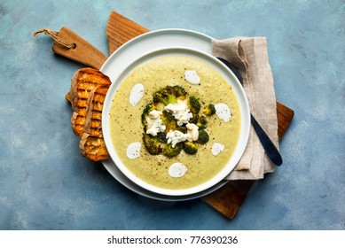 broccoli cheese soup and fresh grilled bread with sour cream and black pepper with gorgonzola on a cutting board on a blue background