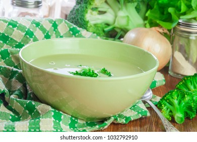 Broccoli cream soup in green bowl on rustic table