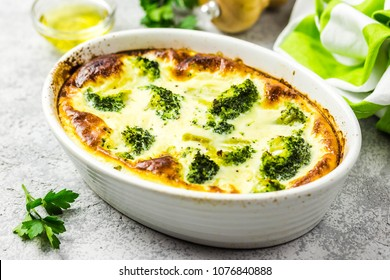 Broccoli egg cheese casserole in baking dish on concrete background. Selective focus, space for text.