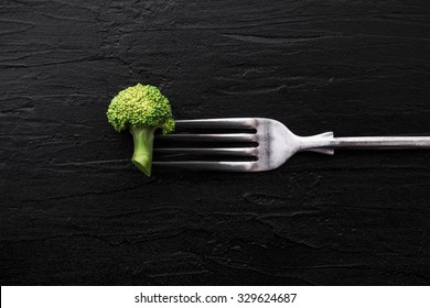 Broccoli with fork on black stone plate background