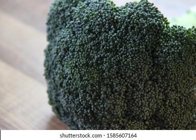 broccoli head on wooden kitchen worktop, closeup view