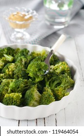 Broccoli with mustard and glass of water, selective focus