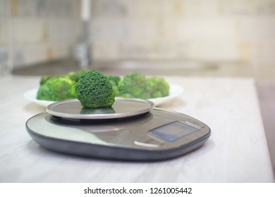 Broccoli on new electronic kitchen scales. Healthy eating concept. Vegan food