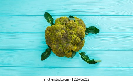 Broccoli on a wooden mint color table.