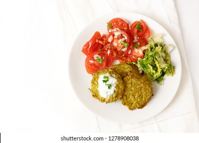 broccoli pancakes with yoghurt dip, lettuce and tomato, healthy slimming food, white plate on a white table with copy space, high angle view from above