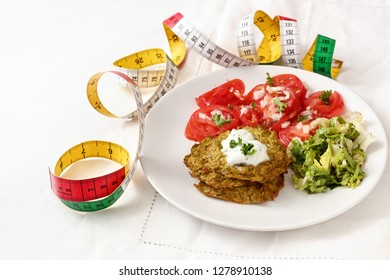 broccoli pancakes with yoghurt dip, lettuce and tomato, and a tape measure, healthy slimming food, white plate on a white tablecloth, selected focus, narrow depth of field