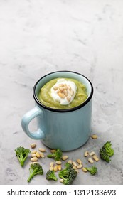 broccoli puree soup with pine nuts in a blue mug, fresh broccoli on a gray background