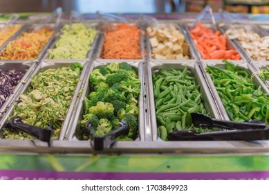Broccoli, snap pea, bell pepper, sliced cabbage trays at salad bar in high-end grocery store near Dallas, Texas, America. Colorful fresh and organic vegetable in self-service counter.