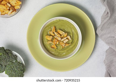 broccoli soup puree with croutons in a white bowl on a green plate on a white background. view from above