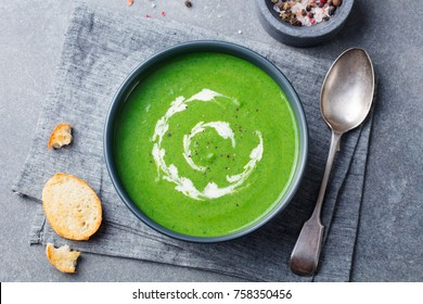 Broccoli, spinach cream soup in a bowl with toasted bread. Top view. Plant based diet.