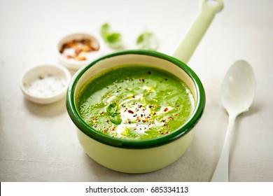Broccoli spinach pea cream soup with cream and chilli flakes