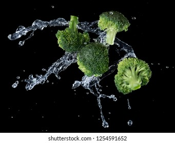 Broccoli with water splash or explosion flying in the air isolated on black background