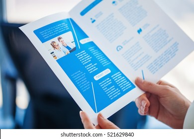 Brochure design. Hands holding a print of a business bi-fold brochure