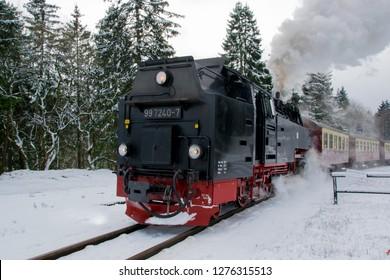 BROCKEN, GERMANY - DECEMBER 17, 2018: Steam engined narrow gauge train at the Brocken Bahn in National Park Harz in Germany during winter