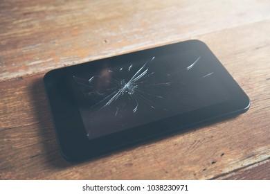 brocken screen tablet on wooden table