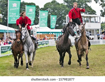 BROCKENHURST, UK - JULY 31: Riders of the Devils Horsemen display race around the show ring standing on the back of two horses at the New Forest & Hants County Show on July 31, 2013 in Brockenhurst