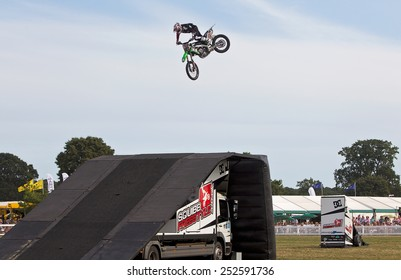 BROCKENHURST, UK - JULY 31: A Squibb FMX team rider completes his stunt jump for the public and makes a successful landing onto the ramp at the New Forest Show on July 31, 2014 in Brockenhurst