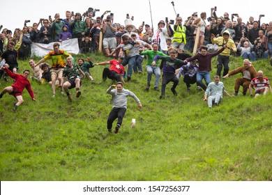 Brockworth, England, UK, May 27th 2019. Eventual winner (front left) Max McDougall chases the cheese during the annual Spring bank holiday cheese-rolling event at Cooper's Hill near Gloucester.