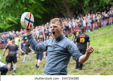 Brockworth, England, UK, May 27th 2019. Canadian Mark Kit celebrates winning the final men's race of the annual Spring bank holiday cheese-rolling event at Cooper's Hill near Gloucester.