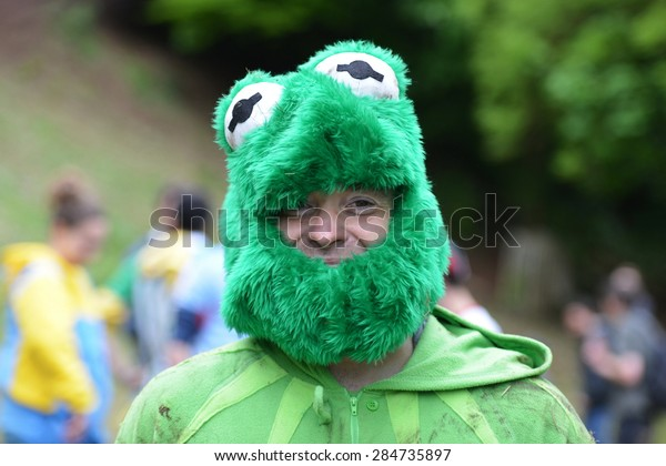 BROCKWORTH - MAY 25: A reveler wearing a Kermit the Frog costume joins the traditional cheese rolling races on May 25, 2015 in Brockworth, UK. The unofficial annual event drew thousands of spectators.