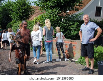 BROEK IN WATERLAND, THE NETHERLANDS – AUGUST 15 2015: Mud race during the annual fair every August in a village north of Amsterdam. After finishing the race the participants jump into the village pond
