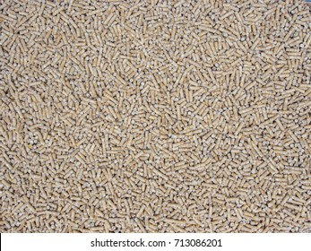 Broiler chicken feed pellets as background.