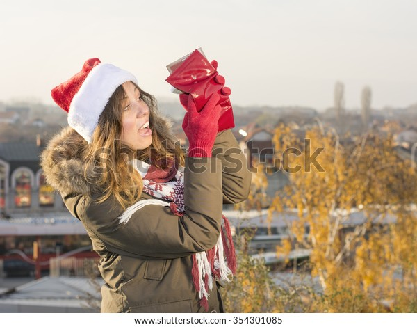 Broke girl for christmas with red wallet and Santa hat
