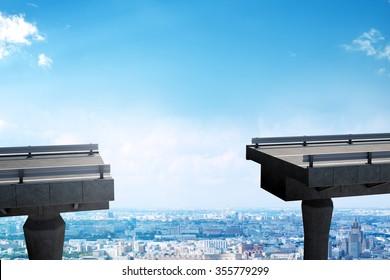 Brokeen bridge with gap above city view
