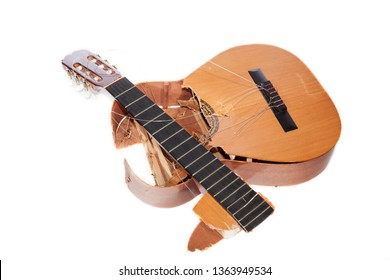 Broken acoustic guitar smashed to pieces. Frustrated angry musician. Demolished classical musical instrument destroyed by a music student guitarist. Isolated against white background.