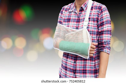broken arm, woman arm bone broken from accident with green cast on arm and arm sling isolated on defocused bokeh lights.