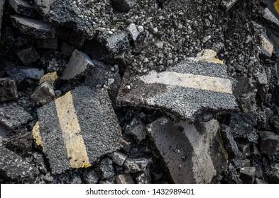 Broken asphalt road showing double yellow lines.
