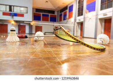 Broken badminton racquet rim with badminton court as background