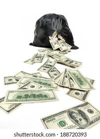 Broken bag of money / studio photography of black plastic bag with hundred dollar bills on a white background