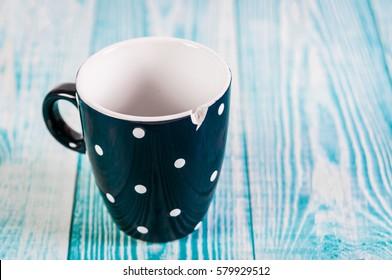Broken black ceramic cup, blue wooden background, free space
