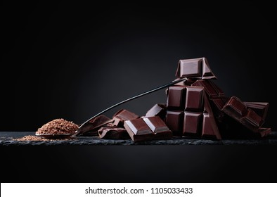 Broken black chocolate pieces and chocolate chip in small spoon on black  background. Copy space.